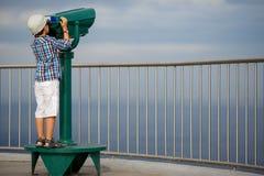 Criança que olha através dos binóculos a fichas Imagem de Stock Royalty Free