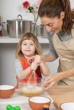 Criança que olha e que chicoteia para fazer um bolo com mãe fotografia de stock royalty free