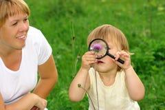 Criança que olha a flor através da lupa Imagem de Stock Royalty Free