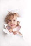 Criança que olha fora de um furo Imagem de Stock