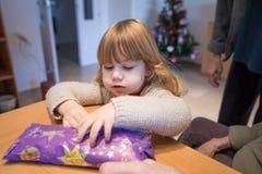 Criança que olha para abrir o presente de Natal envolvido no papel Fotografia de Stock