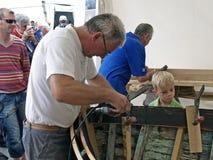 Criança que olha a restauração de madeira velha do barco Fotografia de Stock Royalty Free