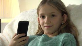 Criança que olha a tevê, menina com relaxamento de controle remoto no sofá, treinador na vida filme