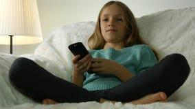 Criança que olha a tevê, menina com relaxamento de controle remoto no sofá, treinador na vida video estoque