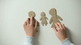 Criança que põe a família e o coração do papel sobre o fundo branco, necessidades órfãos em casa filme