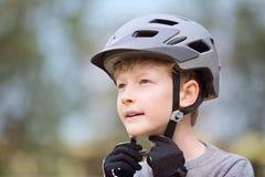 Criança que põe o capacete da bicicleta sobre Imagens de Stock Royalty Free