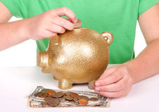 Criança que põr o dinheiro no banco piggy Imagens de Stock Royalty Free