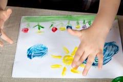 Criança que paiting a pintura com seus dedos foto de stock