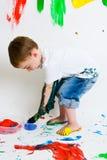 Criança que pinta e que faz um mess Foto de Stock