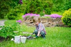 Criança que planta flores no jardim foto de stock royalty free