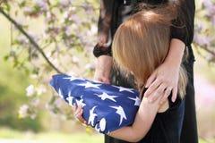 Criança que prende a bandeira americana dobrada de um pai Fotografia de Stock Royalty Free