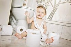 Criança que rasga acima o papel higiênico no banheiro foto de stock royalty free