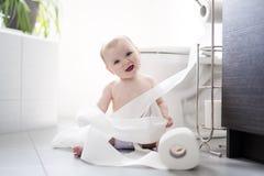 Criança que rasga acima o papel higiênico no banheiro fotos de stock royalty free