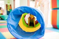 Criança que rasteja através de um túnel foto de stock