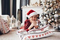 Criança que relaxa pela árvore de Natal em casa Fotos de Stock Royalty Free