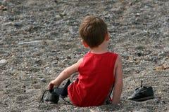 Criança que retira seus instrutores Imagens de Stock