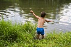 A criança que salta no lago ou na lagoa Fotos de Stock