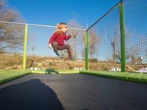A criança que salta no trampolim Fotografia de Stock