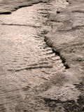 A criança que salta para poças na aproximação amigável das estradas no fim do inverno Foto de Stock
