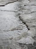 A criança que salta para poças na aproximação amigável das estradas no fim do inverno Imagens de Stock