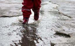 A criança que salta para poças na aproximação amigável das estradas no fim do inverno Imagem de Stock Royalty Free