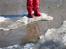 A criança que salta para poças na aproximação amigável das estradas no fim do inverno Fotos de Stock Royalty Free