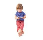 Criança que senta e que joga o smartphone fotografia de stock