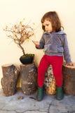 Criança que senta-se ao lado da árvore dos bonsais Fotografia de Stock Royalty Free