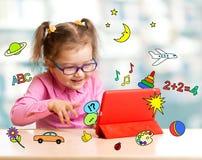 Criança que senta-se com tablet pc e que aprende wi Imagem de Stock