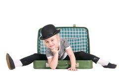Criança que senta-se em uma mala de viagem verde velha imagem de stock royalty free