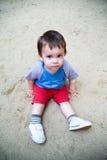 Criança que senta-se na areia Imagens de Stock Royalty Free