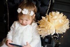 Criança que senta-se na cadeira e que olha entusiasticamente a tela do smartphone Fotos de Stock Royalty Free