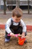 Criança que senta-se na caixa de areia que faz a torta da lama Imagem de Stock