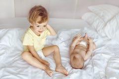 Criança que senta-se na cama perto do infante foto de stock royalty free