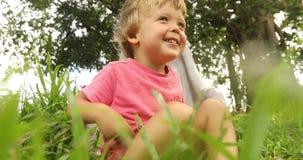Criança que senta-se na grama video estoque