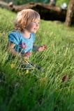 Criança que senta-se na grama Fotografia de Stock