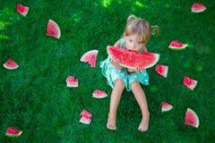 Criança que senta-se na grama e que come a fatia de melancia no verão olhando a câmera Copie o espaço Imagens de Stock Royalty Free
