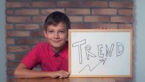 Criança que senta-se na mesa que guarda o flipchart com rotulação da tendência imagem de stock royalty free
