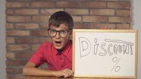 Criança que senta-se na mesa que guarda o flipchart com disconto da rotulação na parede de tijolo vermelho do fundo filme