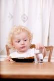 Criança que senta-se na tabela imagens de stock royalty free