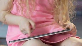 Criança que senta-se no assoalho e que consulta na tabuleta, educação interativa vídeos de arquivo