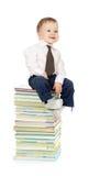 Criança que senta-se no montão dos livros fotografia de stock royalty free