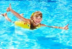 Criança que senta-se no polegar inflável do anel acima. Foto de Stock