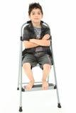 Criança que senta-se nos braços da escada de etapa cruzados fotos de stock royalty free