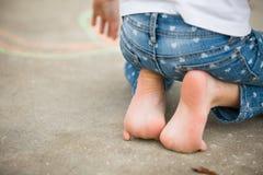 Criança que senta-se nos pés na entrada de automóveis Fotografia de Stock