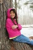 Criança que senta-se sob a árvore no inverno Imagens de Stock Royalty Free