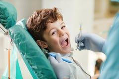 Crian?a que sorri ao sentar-se na cadeira do dentista fotografia de stock royalty free