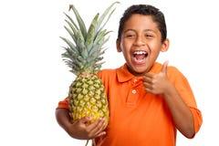 Criança que sorri e que prende o abacaxi com polegar acima Fotografia de Stock Royalty Free