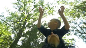 Child smiling while standing on mother shoulders enjoying his recreational time raising hands in air Stock Footage