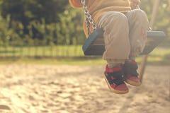 Criança que tem o divertimento com balanço em um campo de jogos no sol brilhante da tarde - os pés dobraram fotos de stock royalty free